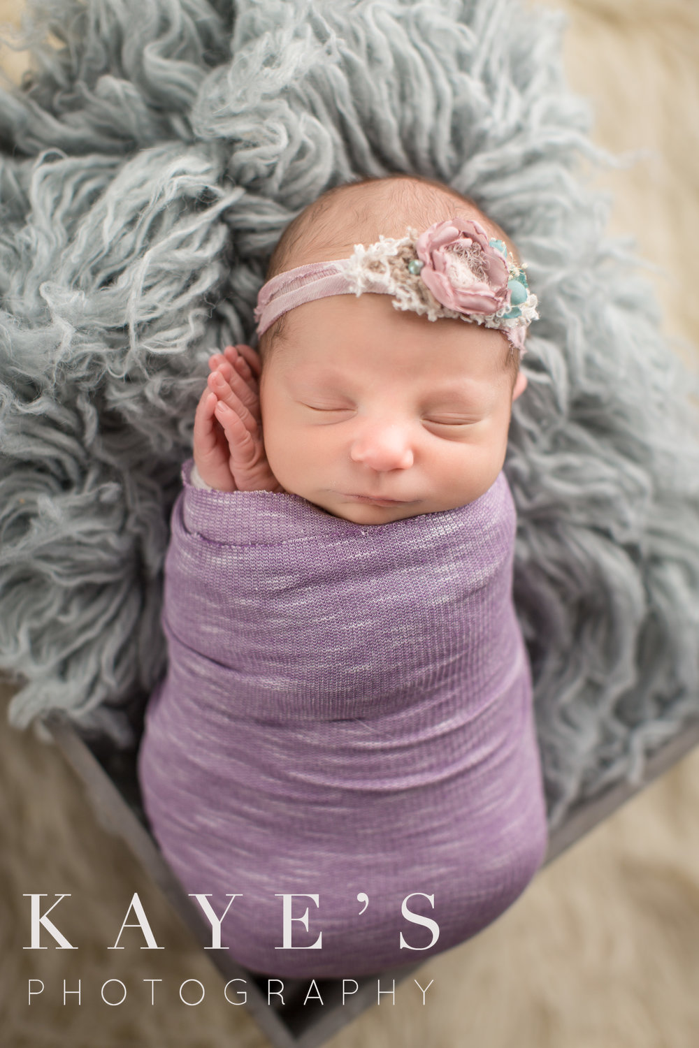 baby girl newborn in purple wrap in basket by grand blanc baby celebrity photographer