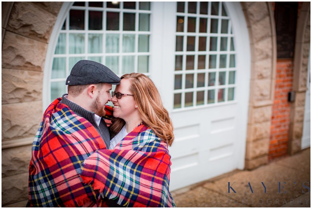Grand blanc, Michigan engagement portrait session with couple in the city hugging during their engagement photos