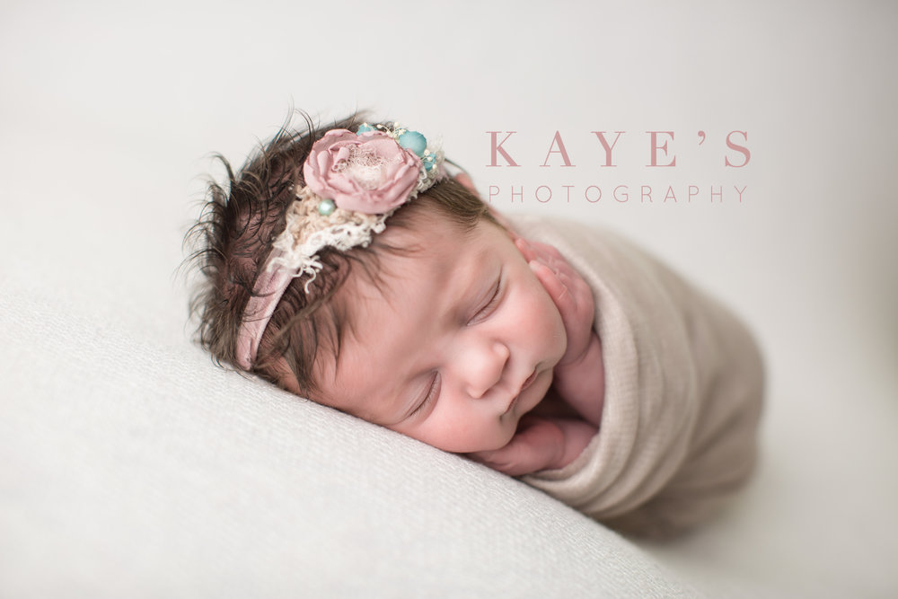 baby girl laying on her side in a cream wrap with pink headband with lots of hair in grand blanc Michigan studio
