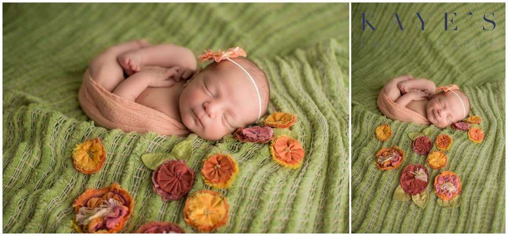 Newborn girl smiling on green blanket wearing headband during studio photography