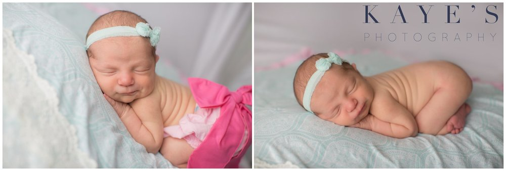 Celebrity newborn girl in studio on blue blanket wearing headband and pink bow