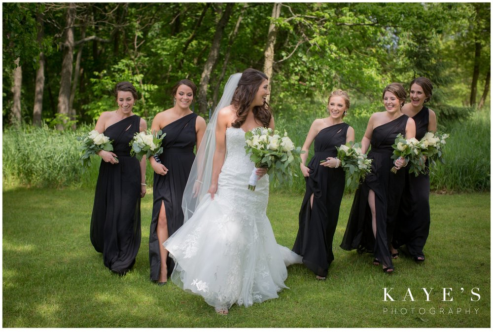 bride and bridemaids walking during a black and white wedding photos