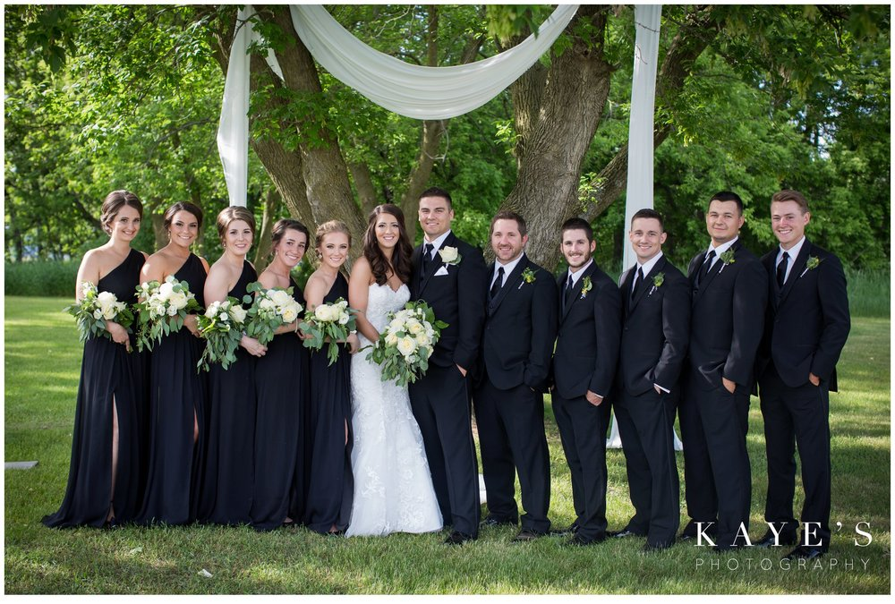 Large bridal party in black and while under a large tree in pontiac Michigan during wedding portraits