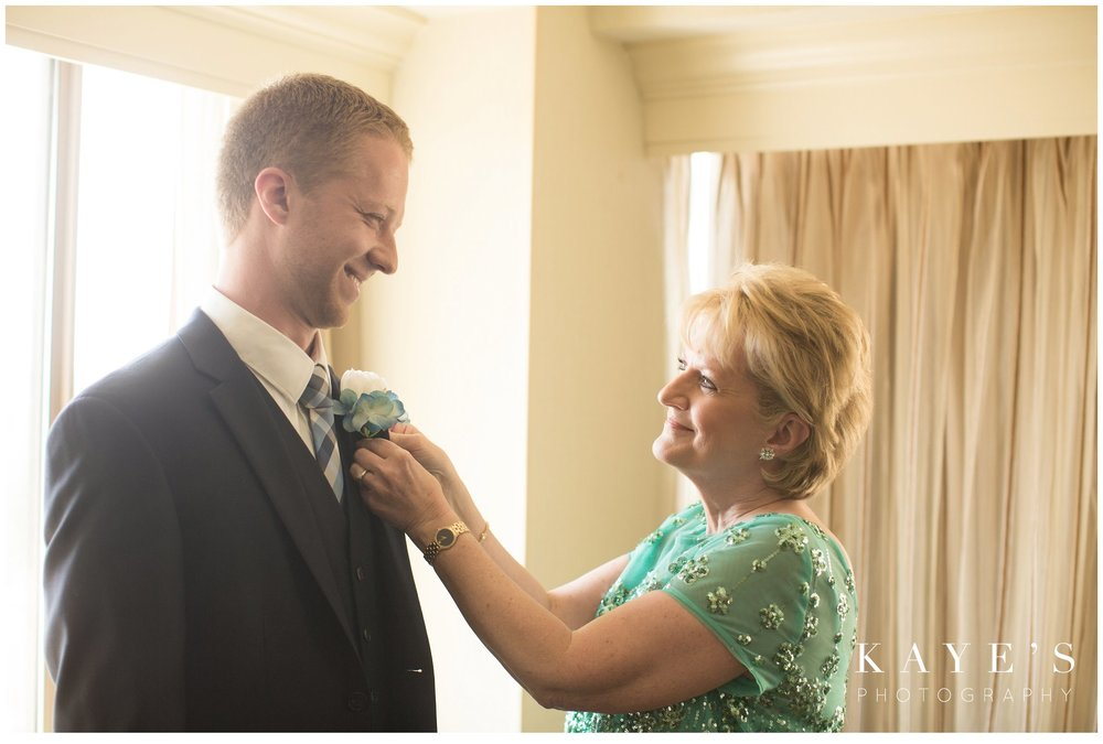 Groom's mother pinning groom while getting ready in plymouth, michigan