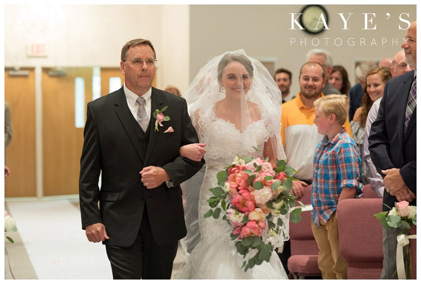 Bride walking up isle with her father during wedding ceremony in Flint Michigan