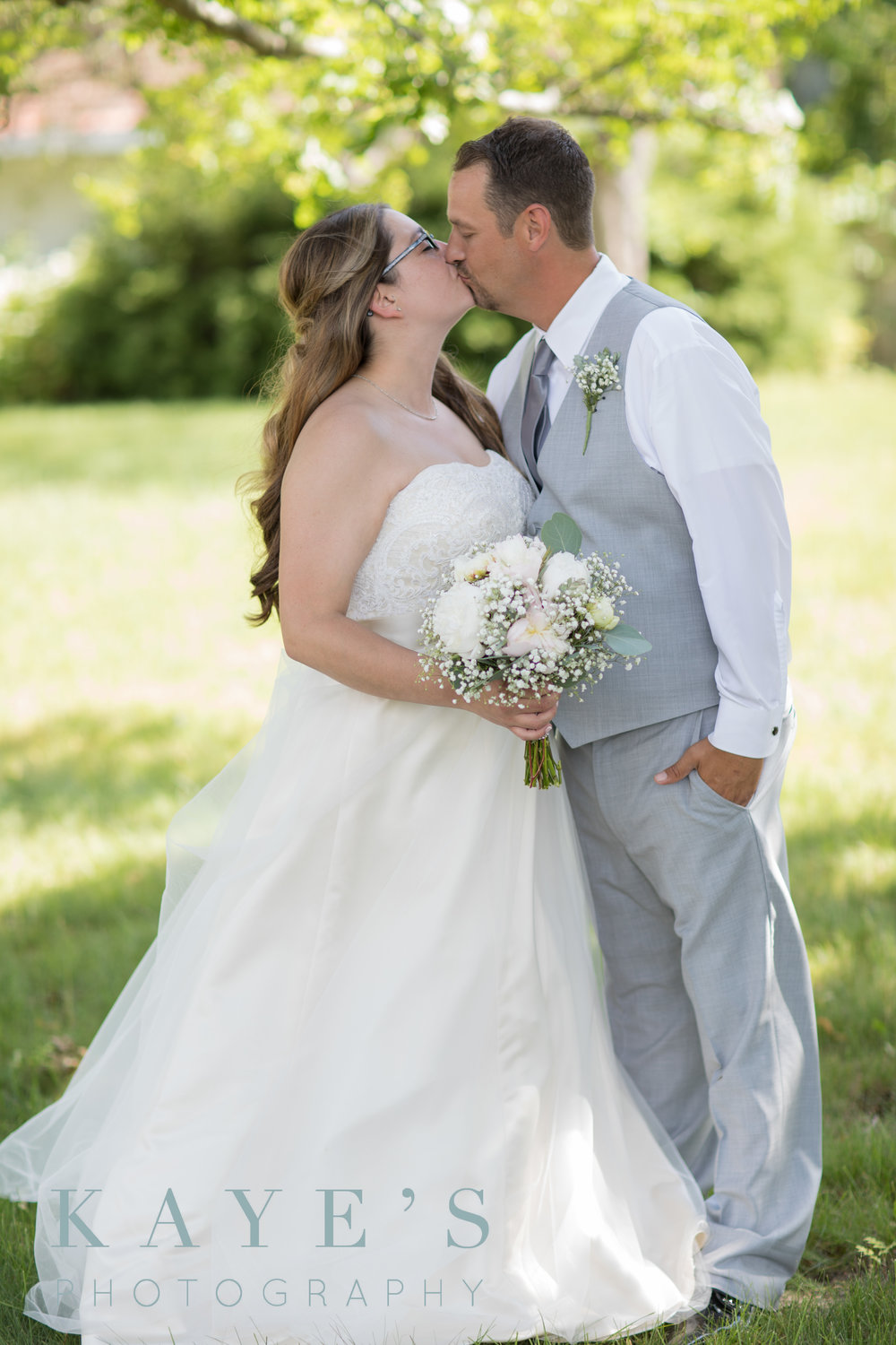 bride and groom kissing in the shade during wedding day photos in holly michigan in during their backyard wedding