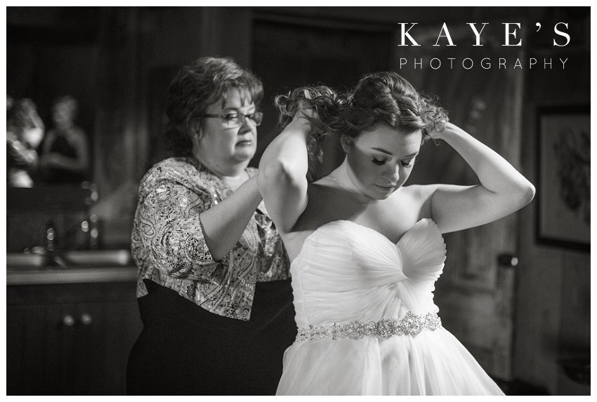 mother putting on brides necklace in ann arbor michigan during wedding