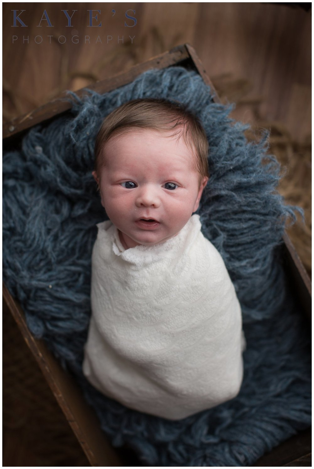 Baby boy in crate on blue rug with eyes wide open