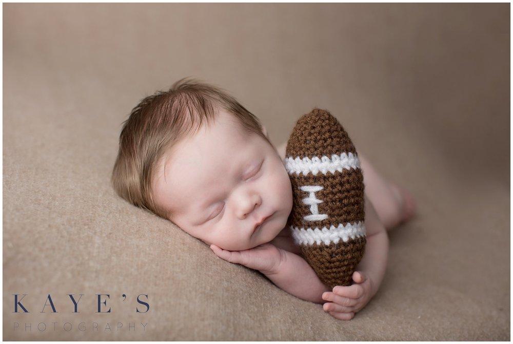 Baby boy with football on tan blanket sleeping