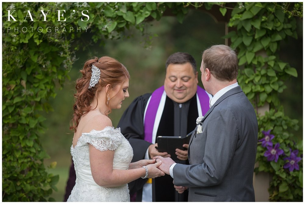 bride putting grooms ring in detroit michigan wedding