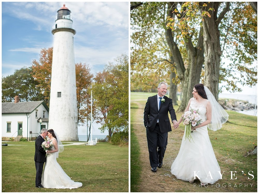 Bride and groom posing in front of the port aux barques lighthouse in Port Hope in Michigan on wedding day