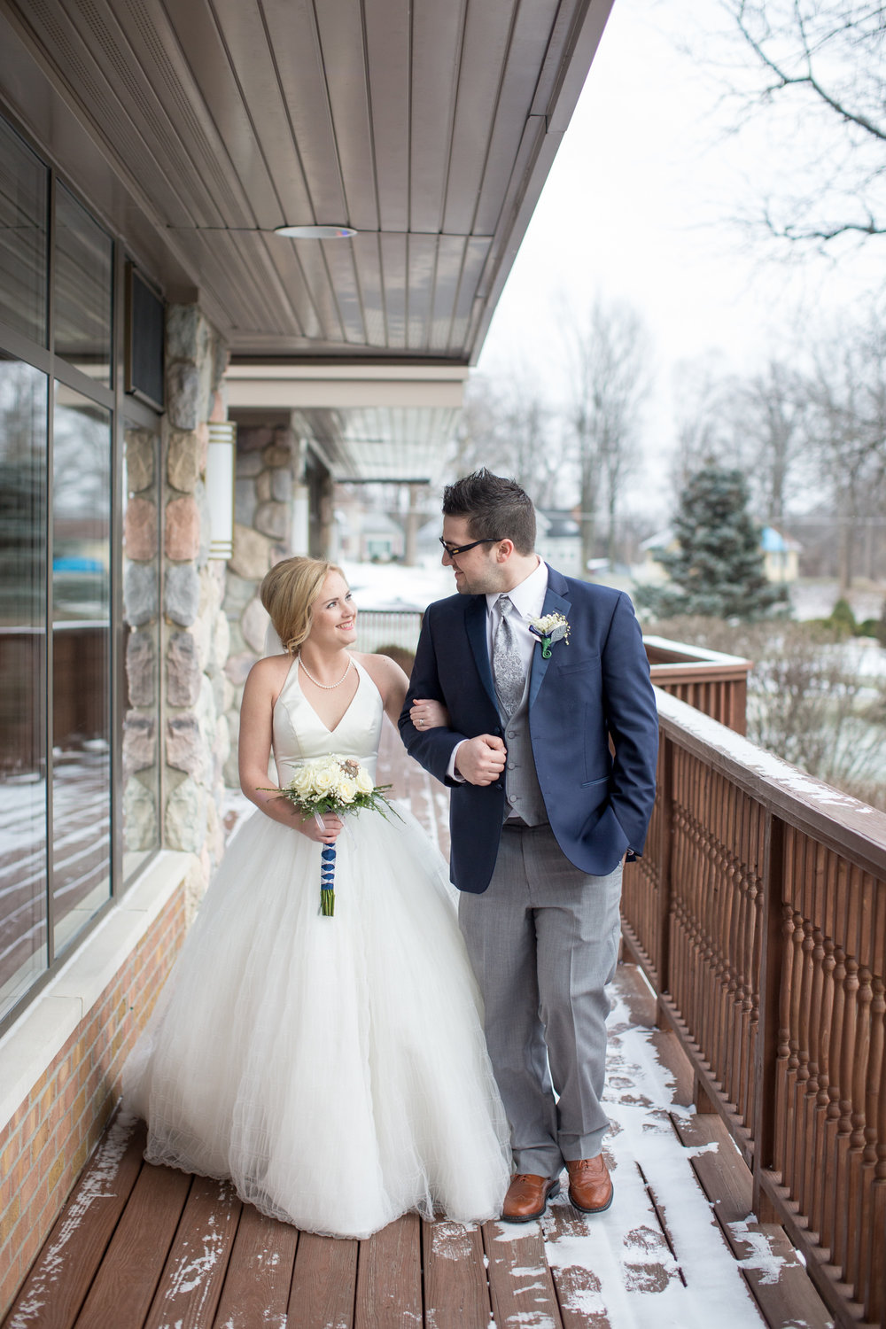 bride and groom in winter walking for wedding photos in Detroit Michigan