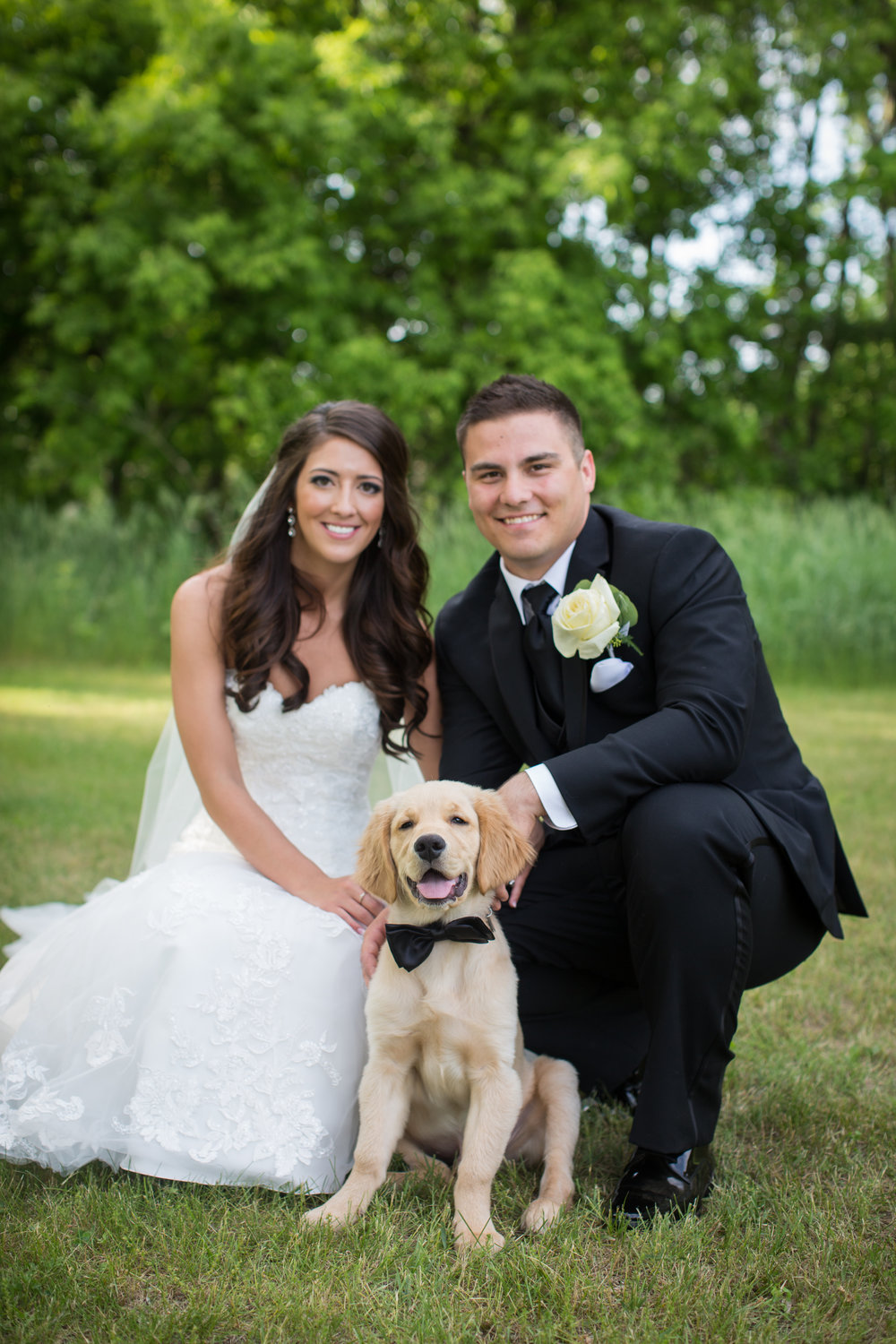bride and groom with their puppy during wedding pictures