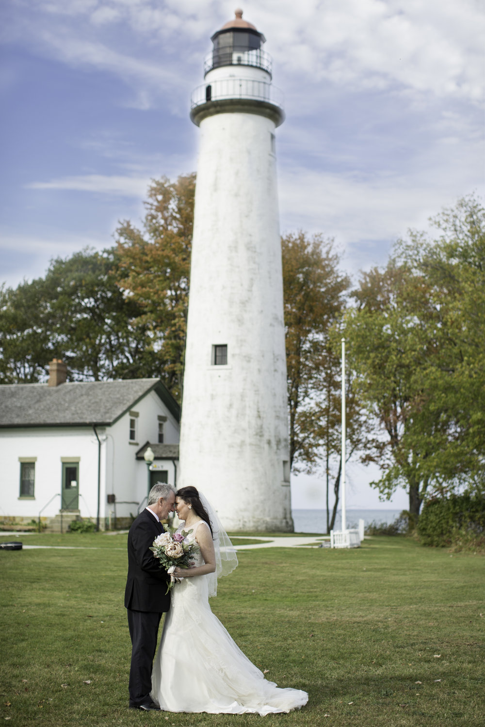 bride and groom taking wedding photos in front of a lighthouse in the fall