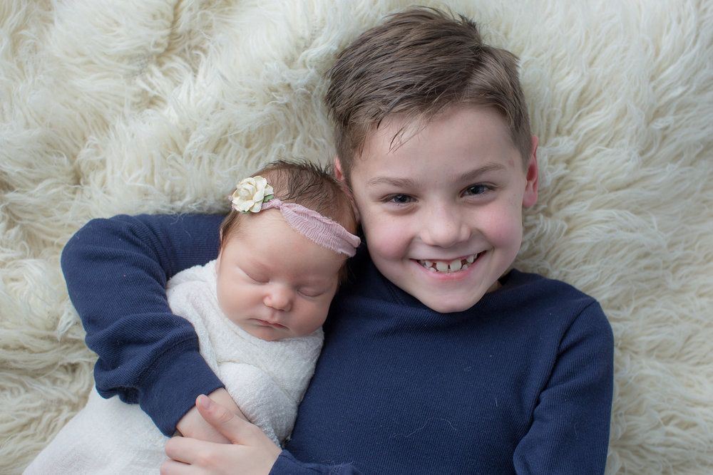 big brother with little sister during baby portraits in flint michigan with kaye's photography