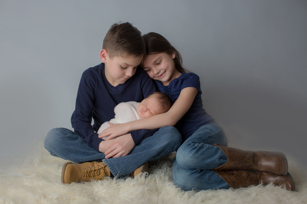 Big brother and sister with baby during newborn session in flint michigan with Kaye's Photography