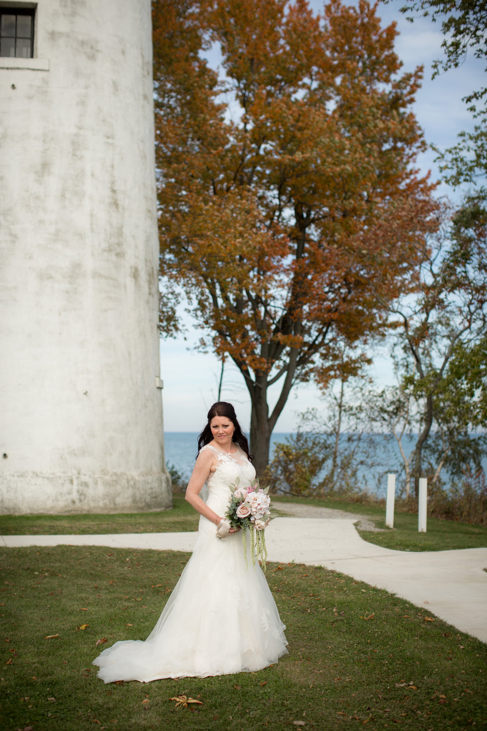 Bride posing next to light house during wedding photos with a St Clair Shores Michigan photographer