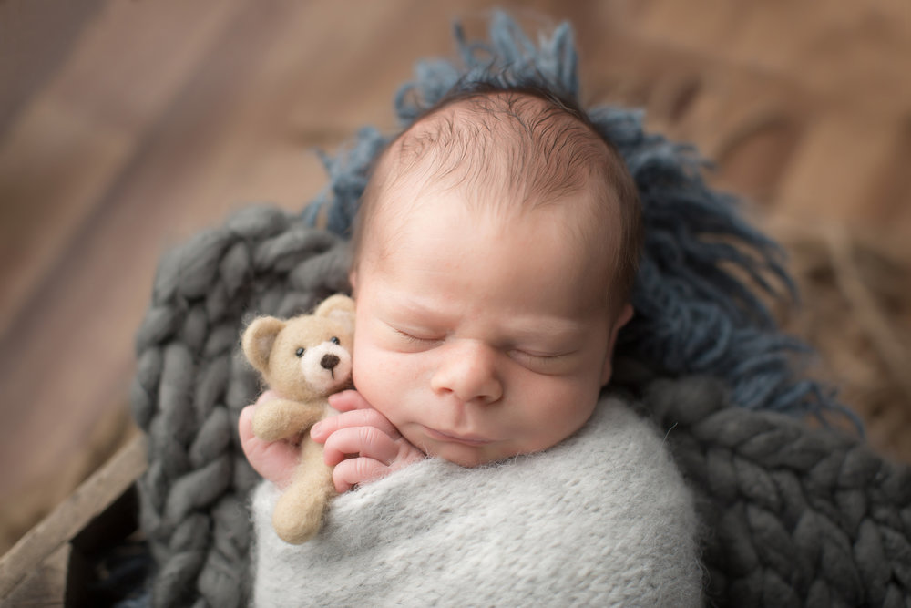baby boy snuggling with bear wrapped in blanket during newborn baby pictures