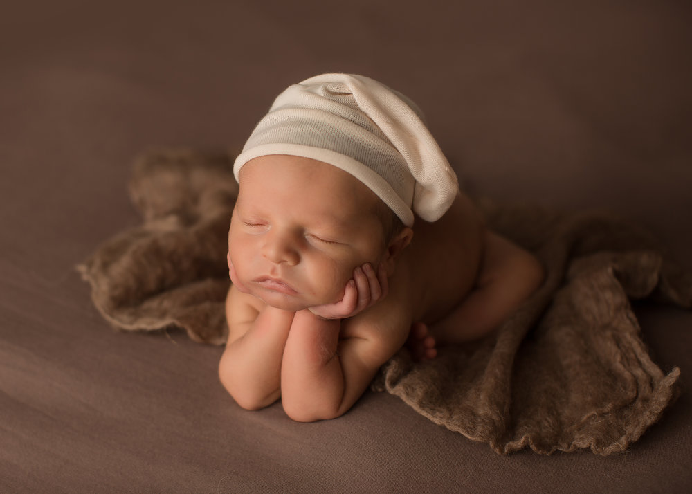 Baby boy wearing hat during newborn baby photos in flint michigan