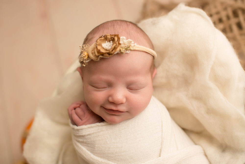 Newborn baby girl smiling during baby pictures in flint michigan