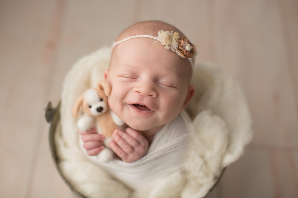 newborn baby girl smiling with little puppy during baby photos in Flint Michigan
