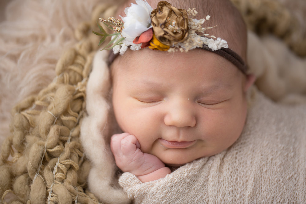 baby girl smiling during newborn baby photos in flint michigan