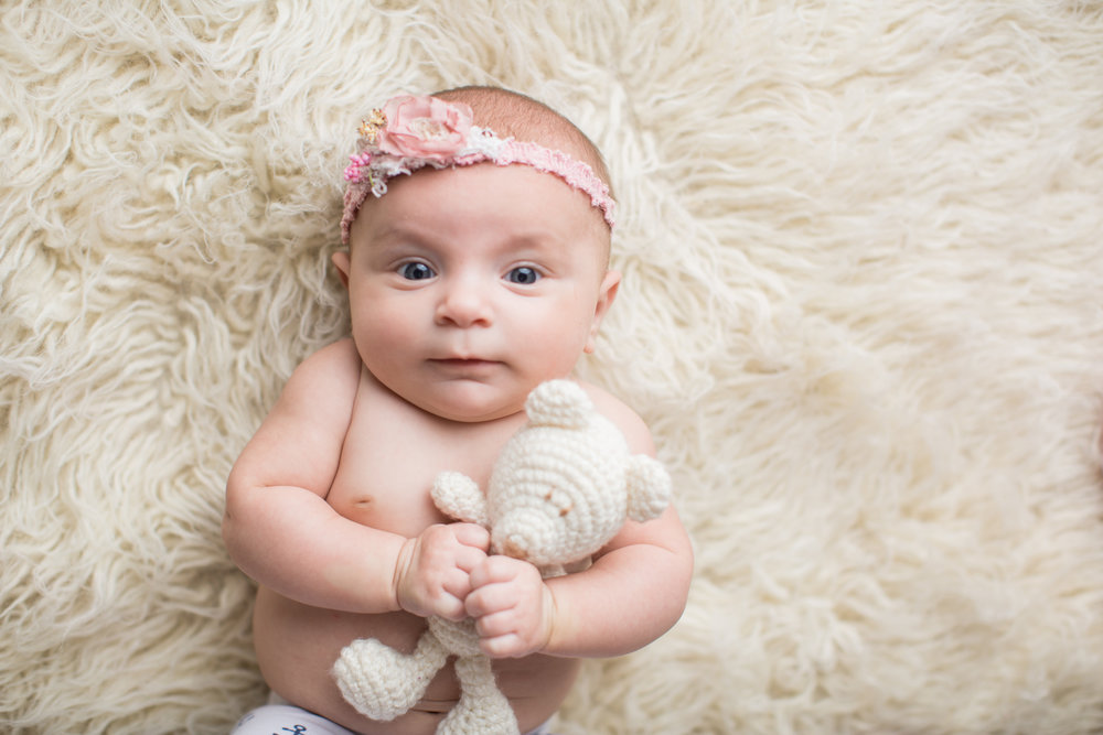 baby girl holding a bear during professional photos in grand blanc Michigan