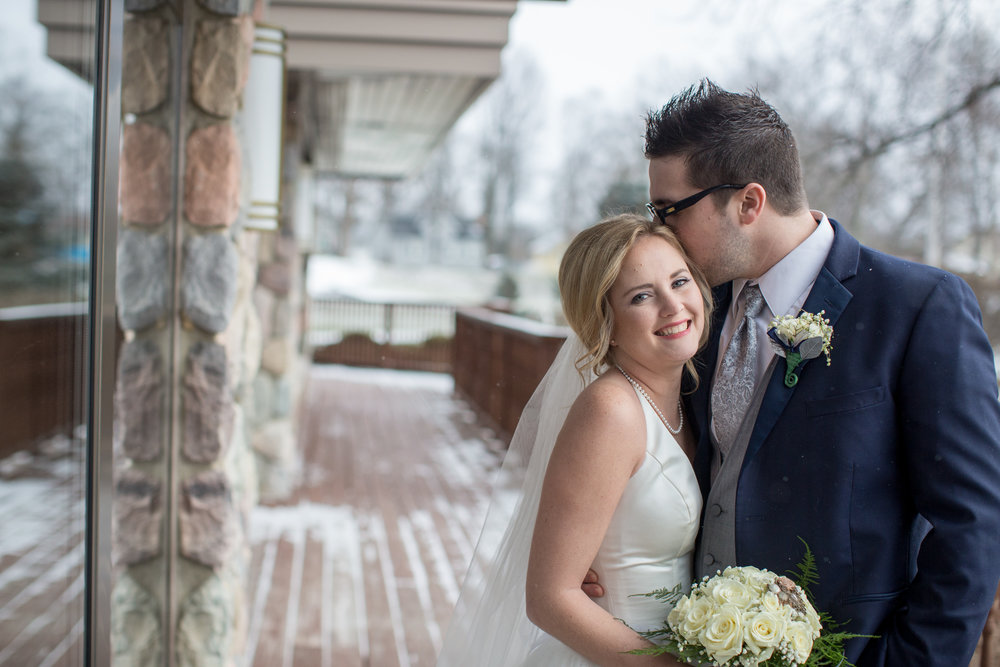 Bride and groom kissing for wedding pictures during winter wedding