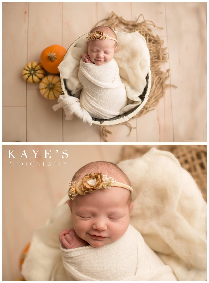 newborn baby girl smiling during baby photo session with pumpkins