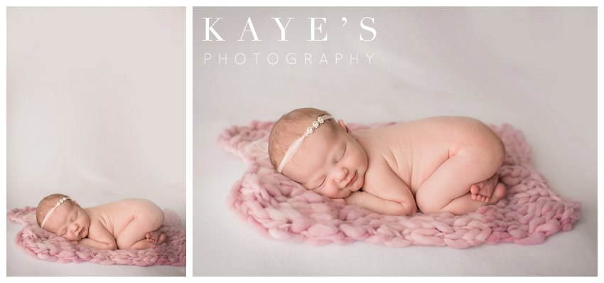 Newborn girl posing on pink blanket and smiling during professional baby pictures