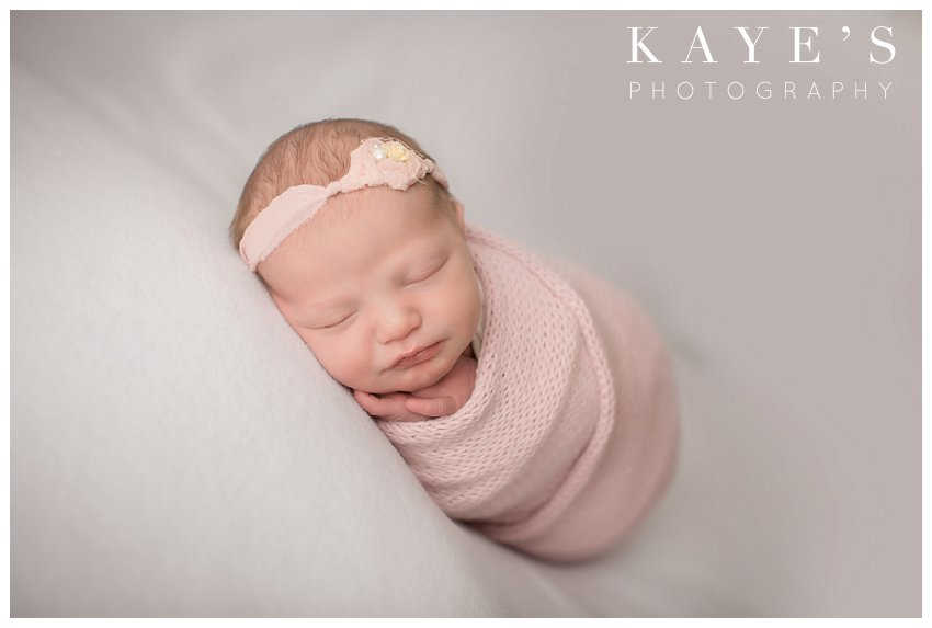 Newborn girl posing on white blanket during professional baby photos