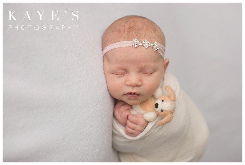 Newborn girl holding puppy during baby photos