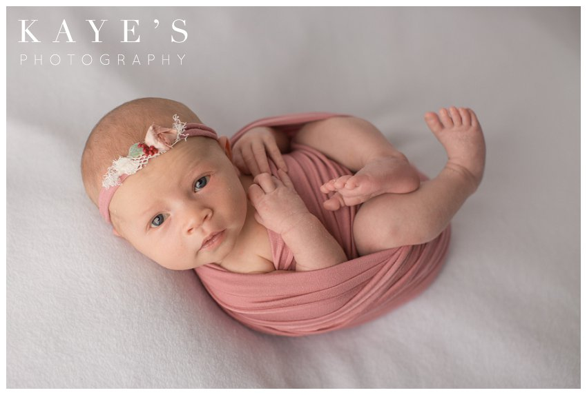 Newborn girl wrapped in pink posing during baby photos