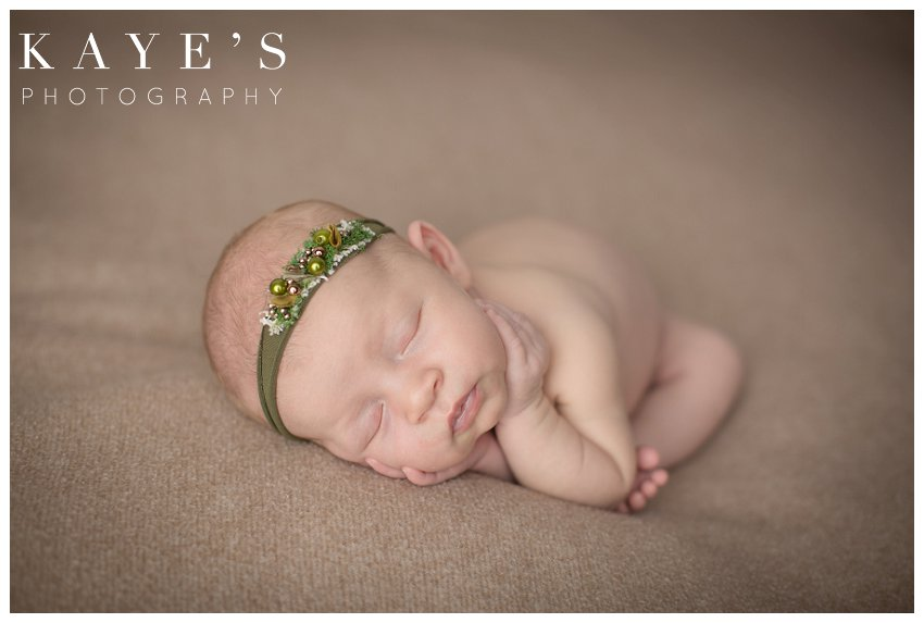 Newborn girl on tan blanket during baby photos