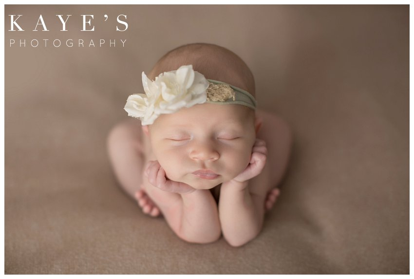 Newborn girl on tan blanket with chin in her hands during professional baby photos
