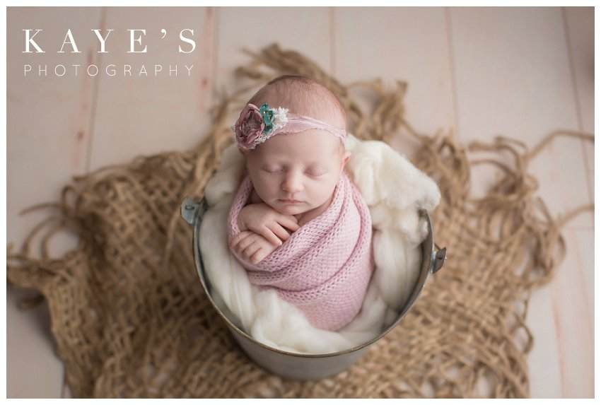 baby girl posing in bucket during newborn photo session in grand blanc Michigan