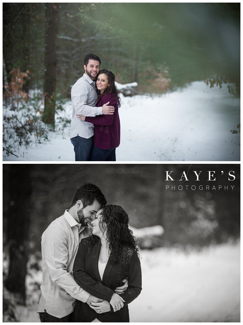couple cuddling and posing for engagement pictures during snowy winter