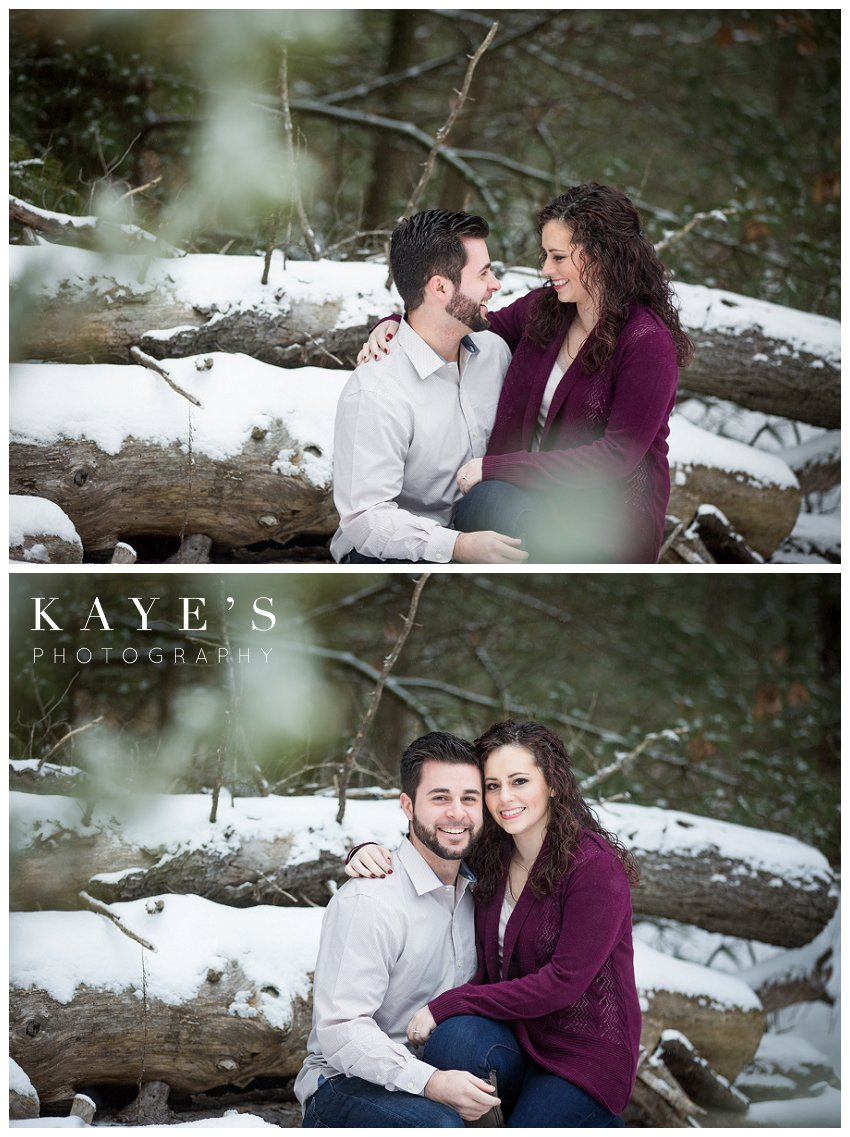 couple cuddling in the snow for winter engagement photos