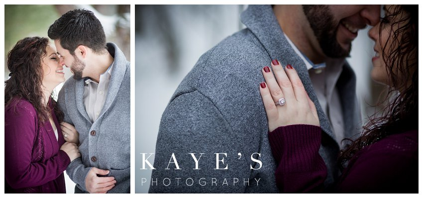 couple kissing and showing off ring during winter engagement pictures in grand blanc Michigan