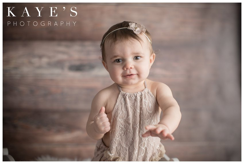 baby girl posing for one year old professional photos