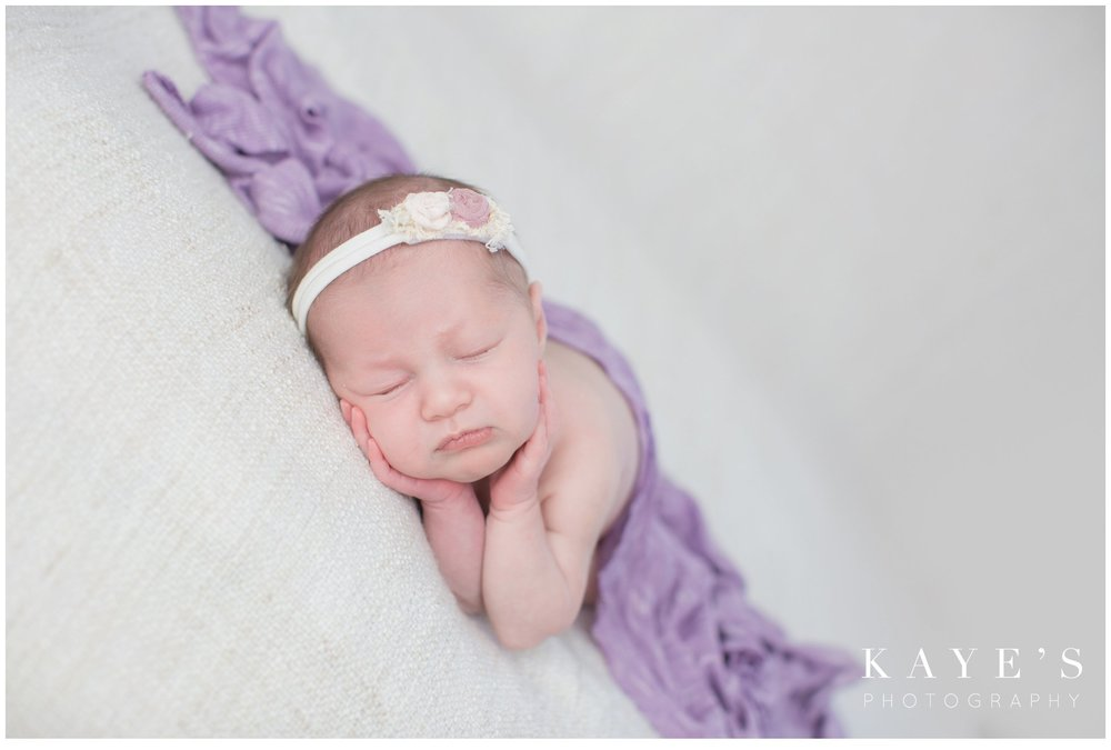 Newborn girl in purple posing for professional baby pictures
