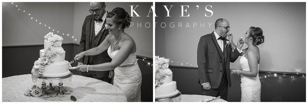Bride and groom cutting their cake during wedding reception at crossroads village!