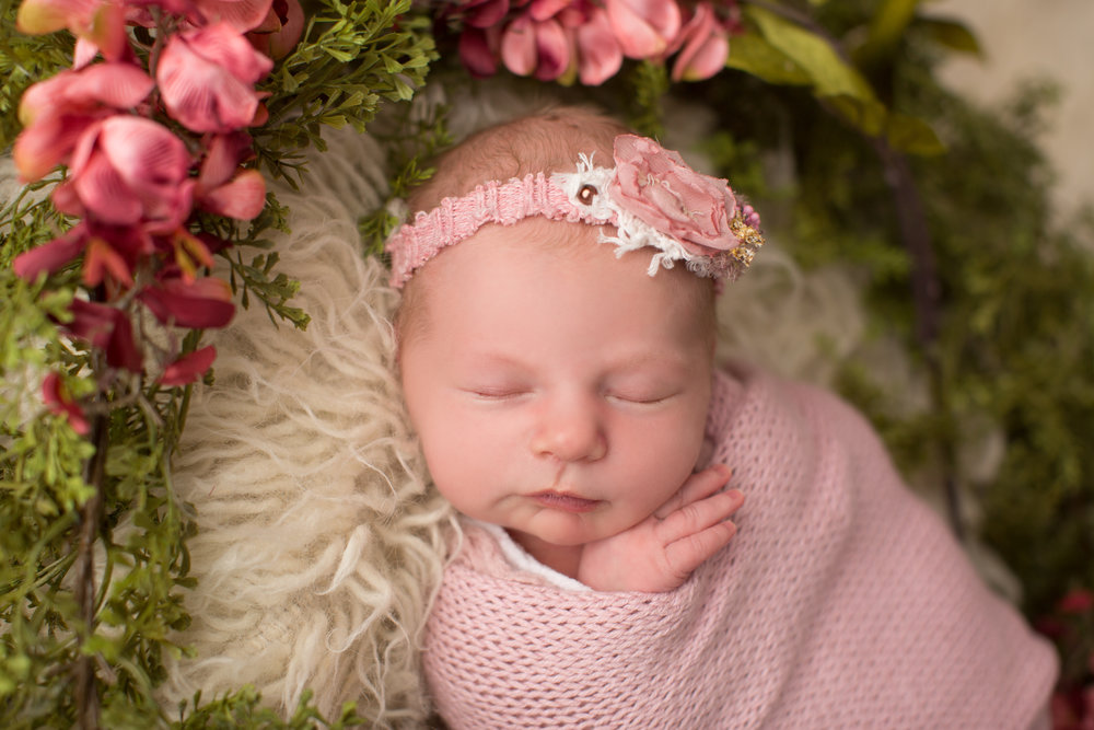 baby girl with pink flowers wrapped during newborn session with headband by kaye's photography