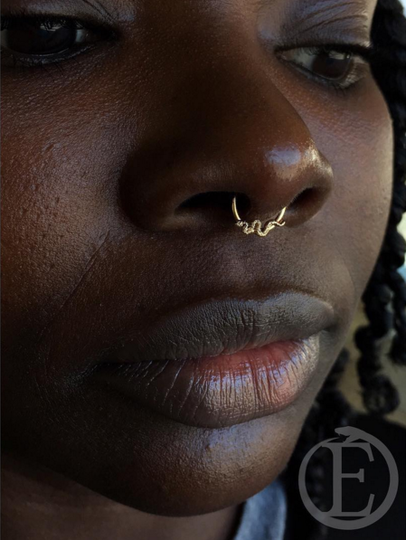 unique septum piercing with a yellow gold seamless ring with a snake!