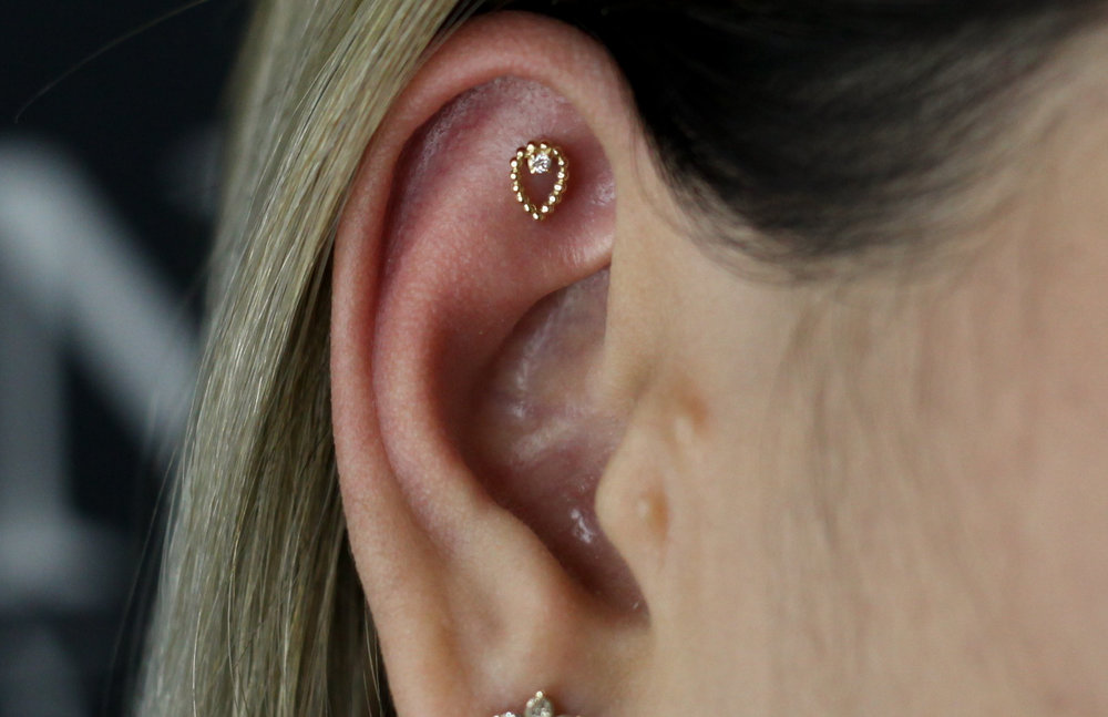 Flat Piercing - Flat, or Scapha piercings, are placed across the flat higher ridge of the ear, inwards from the helix. This is an excellent spot for displaying larger pieces of jewelry. This piercing has a 6-9 month healing time.