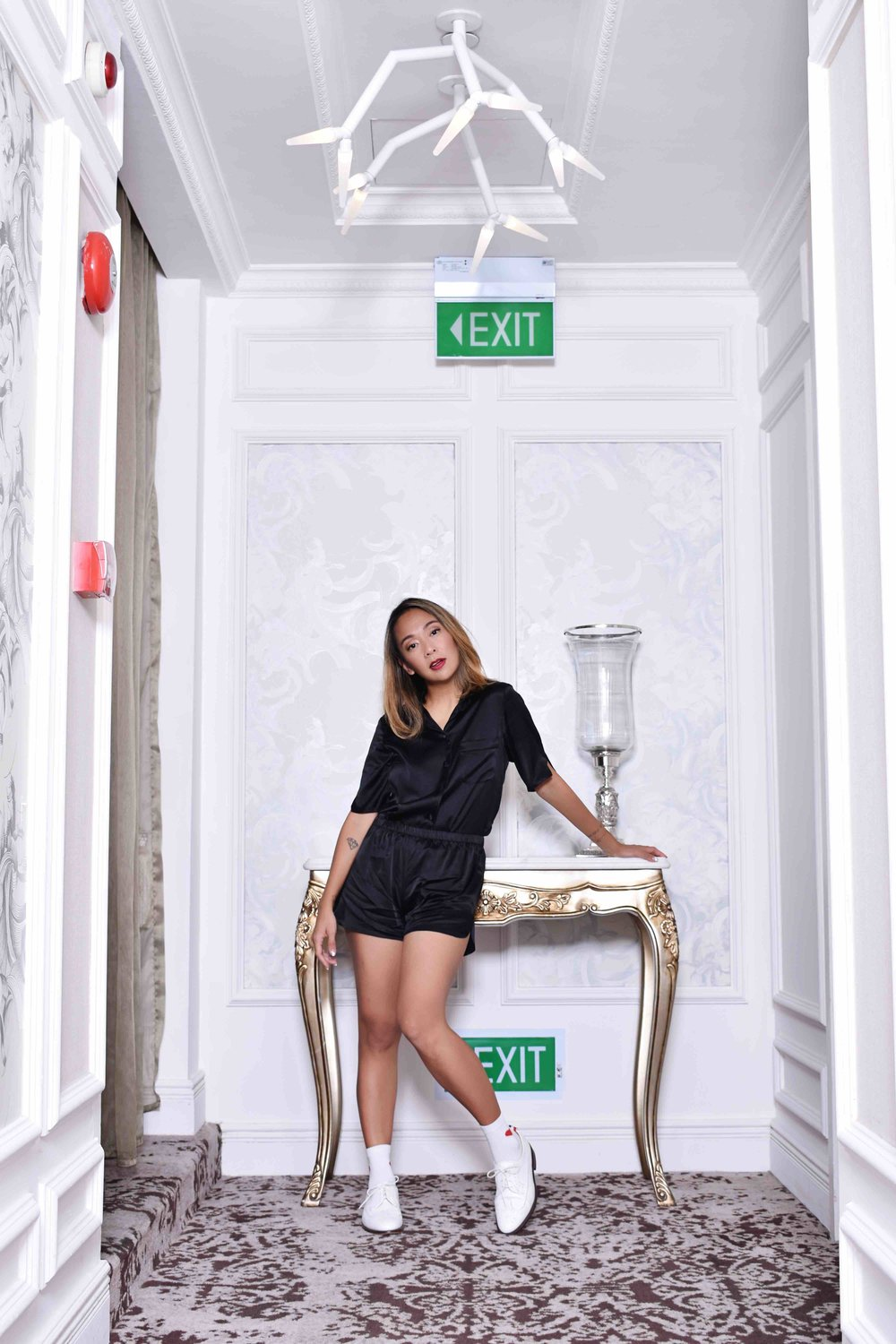 Charmaine wears the ELOISE Silk Jacket & FANG Silk Shorts in Black and her own socks and shoes