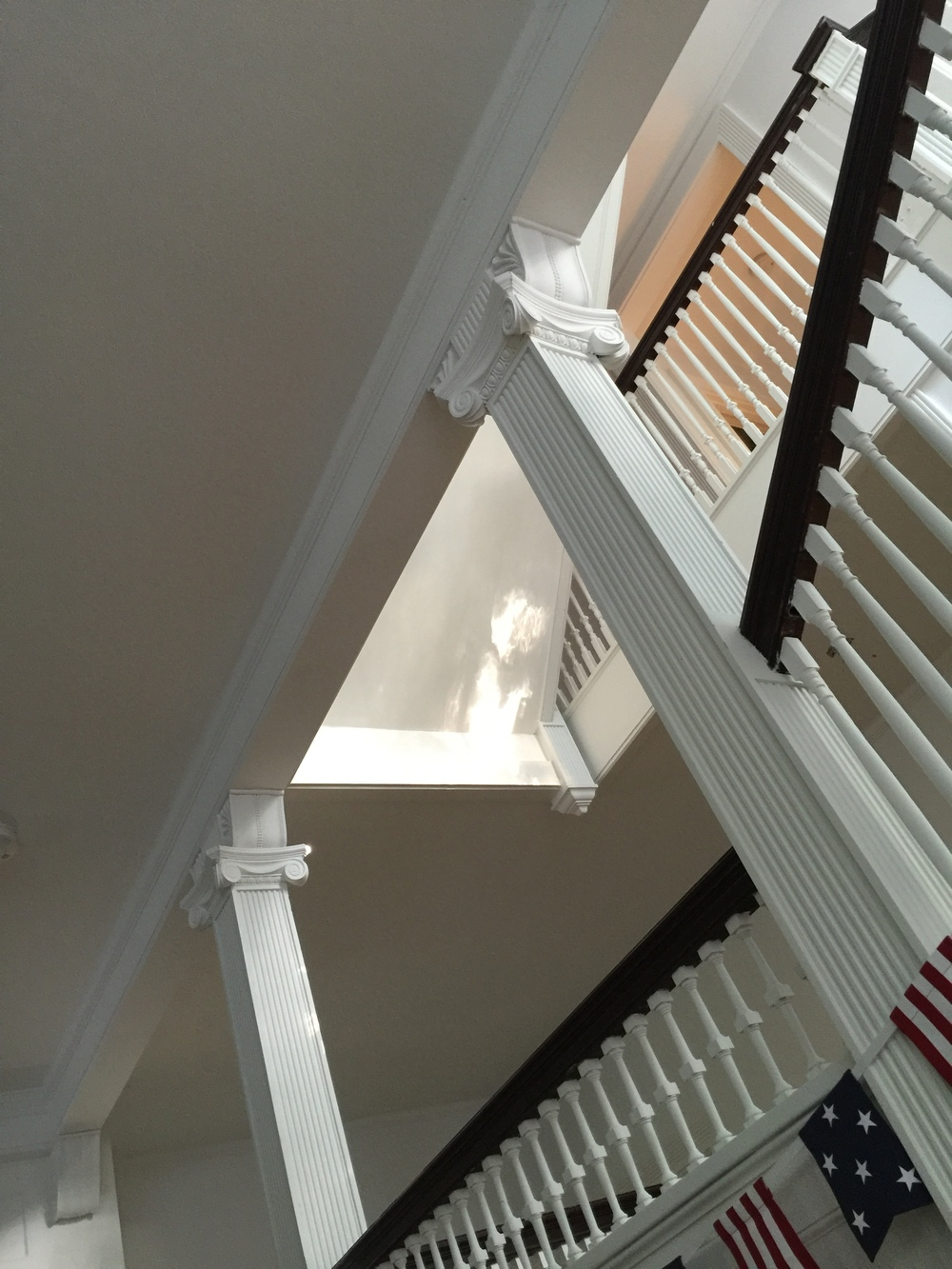 We can't help but appreciate the architectural detail within the columns and railings of the gracious stairwell.