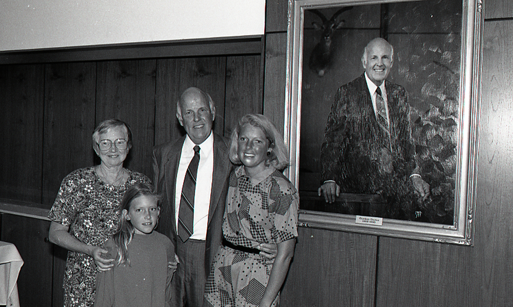 Guyer poses with family in front of his portrait painting at the John A. Hannah administration building at MSU. Photo courtesy of MSU Archives.