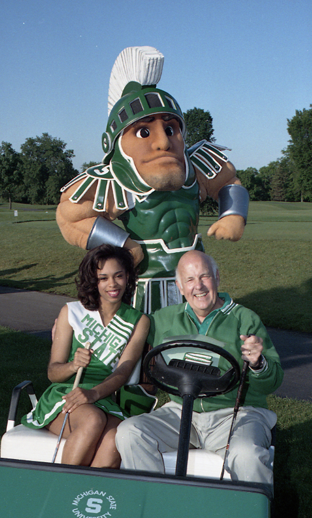 Guyer poses with Sparty and a student during a golf outing. Photo courtesy of MSU Archives.