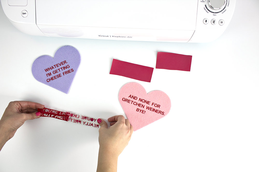 Cricut iron-on vinyl is actually pretty simple to use, as long as you know which way the vinyl goes and how to make sure your letters aren't backwards. Click for the full tutorial, along with how to make some Mean Girls conversation hearts!